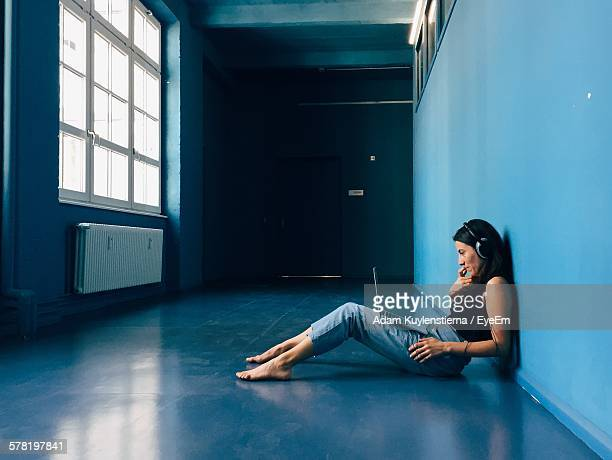 Side View Of Businesswoman Using Laptop While Sitting On Floor In Startup Office