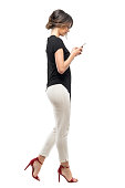 Side view of busy business woman in formal suit walking and typing on mobile phone. Full body length portrait isolated on white studio background