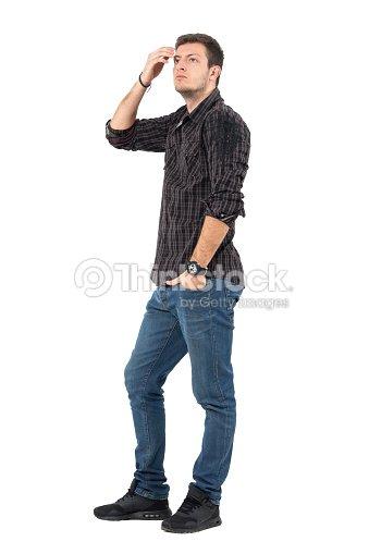 Vista lateral del ocasional hombre joven en jeans y camisa a cuadros ajuste  de pelo con b33cf145ff1