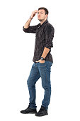 Side view of casual young man in jeans and plaid shirt adjusting hair with hand looking up. Full body length portrait over white studio background.