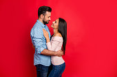 Side view of caucasian, attractive, smiling couple - bearded man embrace his charming, cute, pretty woman, looking to each other while standing over red background, 14 february