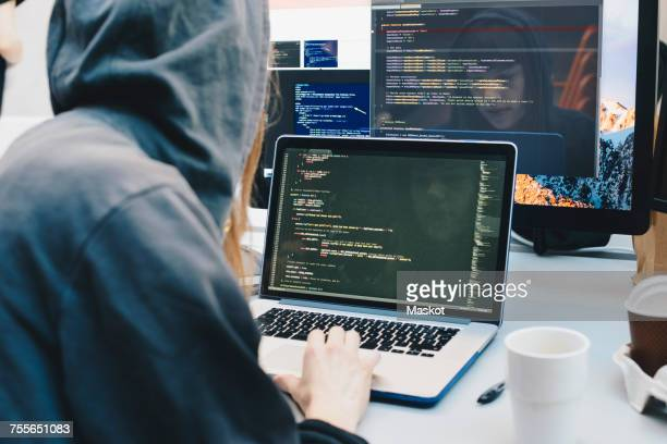 Side view of computer programmer programming on laptop at desk in office