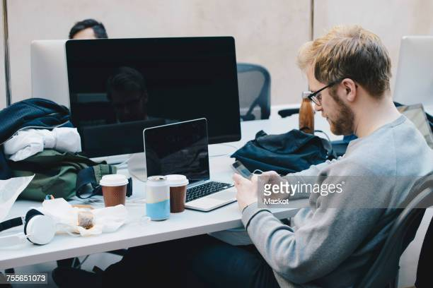 Side view of computer programmer using smart phone at desk in office