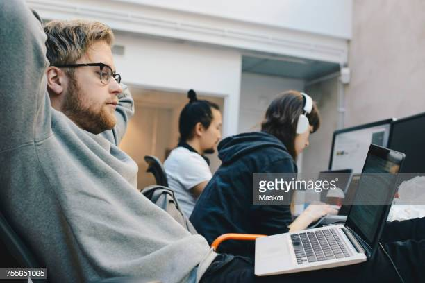 Side view of computer programmers working in office