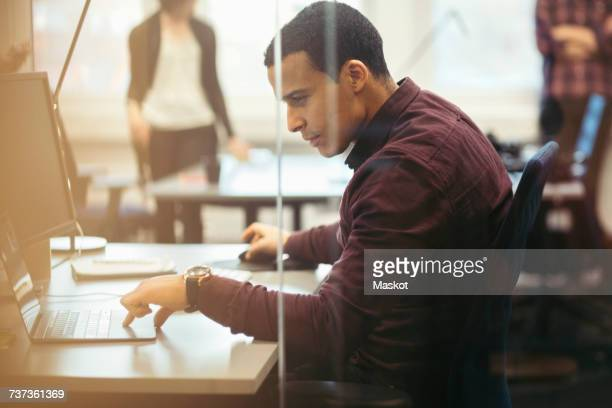 Side view of concentrated businessman using laptop at desk in office