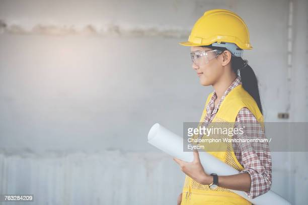 Side View Of Confident Female Engineer Standing With Blueprint At Construction Site