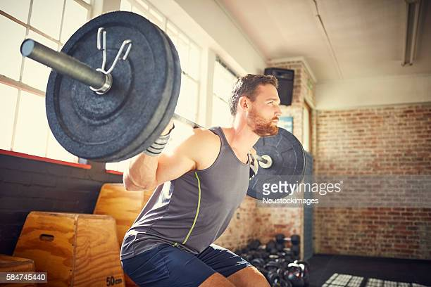 Side view of confident man picking up barbell in gym