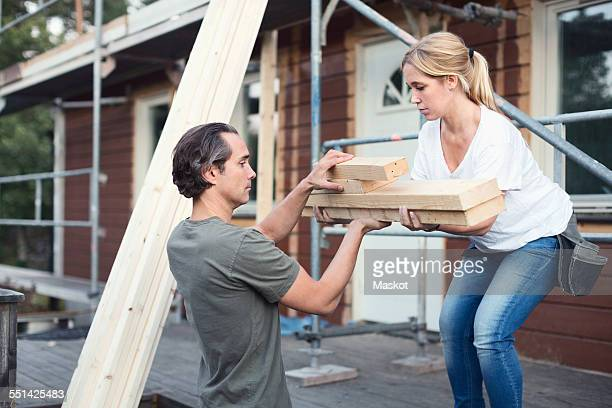 Side view of couple carrying stack of lumber outside house being renovated