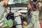 Side view of couple holding camping equipment against car