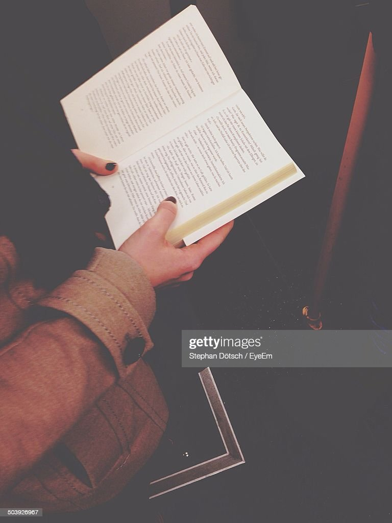 Side view of cropped person reading book