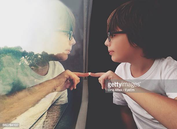Side View Of Cute Boy With Reflection On Train Window