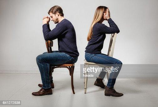 seitenansicht des depressiv paar sitzen r cken an r cken auf st hlen stock foto getty images. Black Bedroom Furniture Sets. Home Design Ideas
