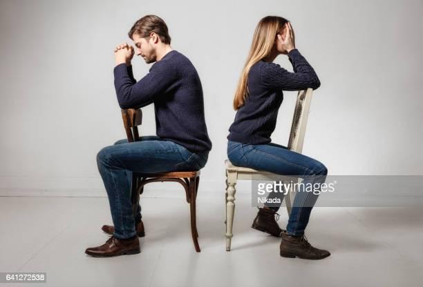 Seitenansicht des depressiv paar sitzen Rücken an Rücken auf Stühlen
