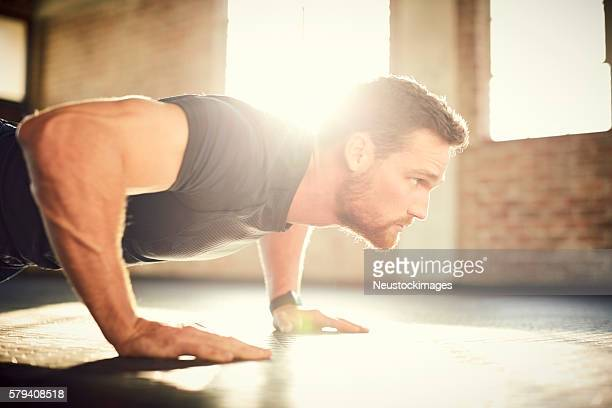 Side view of determined man doing push-ups in gym gym