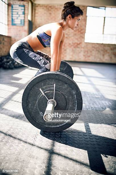Side view of determined woman deadlifting barbell in gym