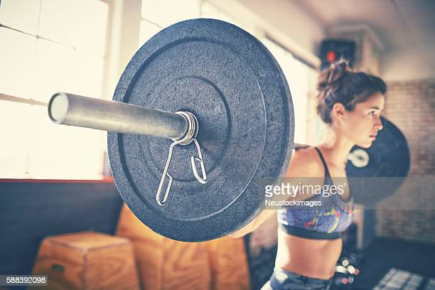 Side view of determined woman picking up barbell in gym
