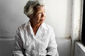 Side view of elderly asian woman with thoughtful face expression