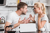 side view of emotional young couple arguing and looking at each other in kitchen, relationship difficulties concept