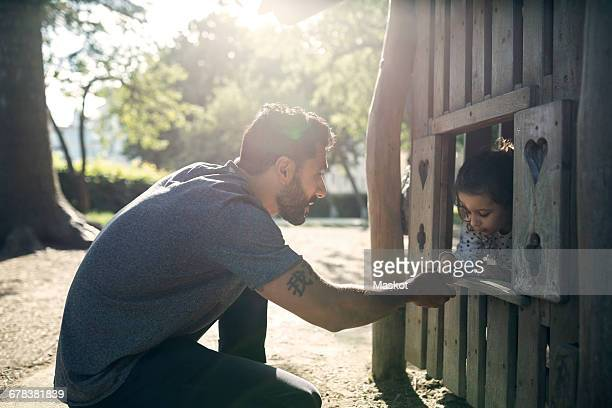 Side view of father and daughter playing in wooden toy house