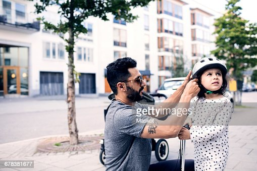 Side view of father assisting daughter in wearing helmet at sidewalk