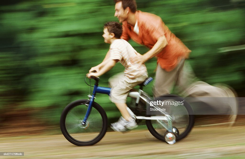 Side view of father teaching son how to cycle bicycle (10-11) : Stock Photo