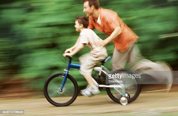 Side view of father teaching son how to cycle bicycle (10-11)