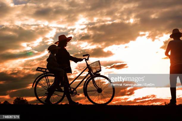 Side View Of Father With Daughter On Bicycle Leading Towards Man In Field