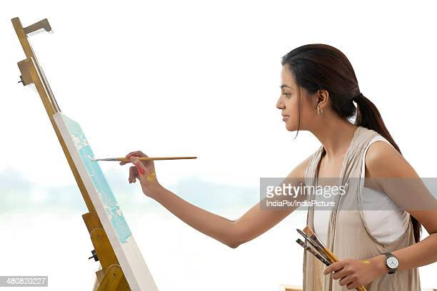 Side view of female artist painting on canvas over white background