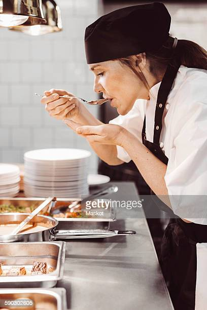 Side view of female chef tasting food at commercial kitchen