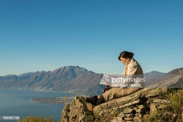 Side View Of Female Hiker With Map Sitting On Cliff Against Swiss Alps