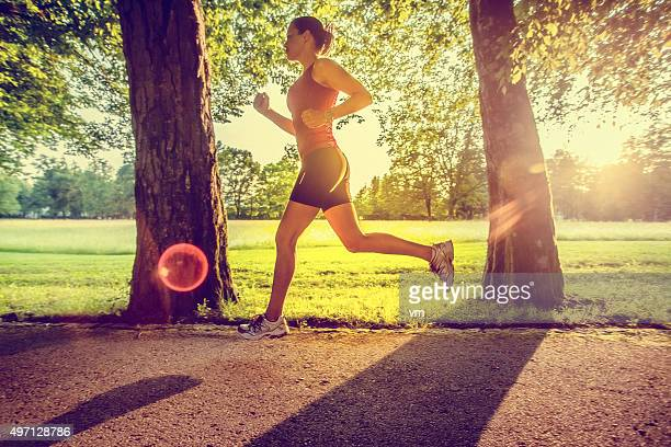 Side view of female jogger in mid-air in a park