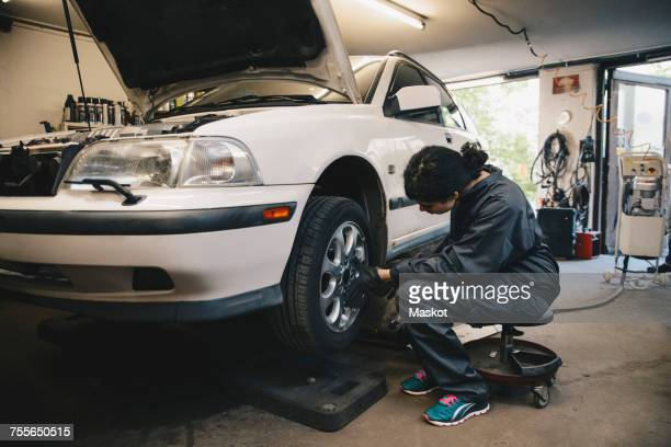 Side view of female mechanic examining car wheel at auto repair shop
