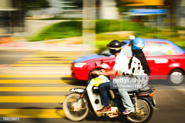 Side View Of Friends Sitting On Motorcycle