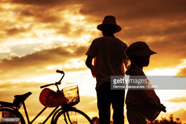 Side View Of Girl By Father And Bicycle Against Orange Clouds In Sky At Sunset