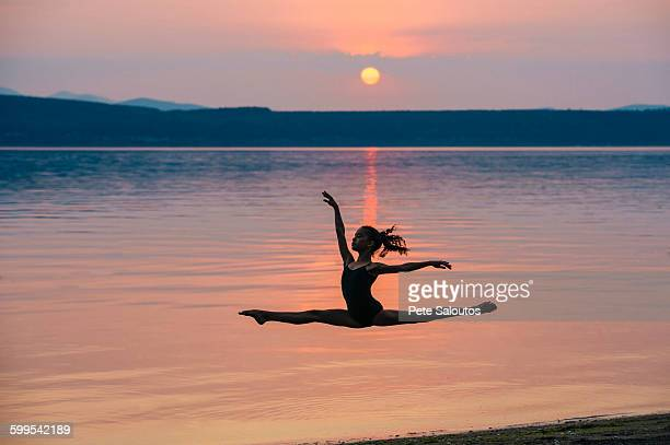 Side view of girl by ocean at sunset leaping in mid air, arms raised doing the splits