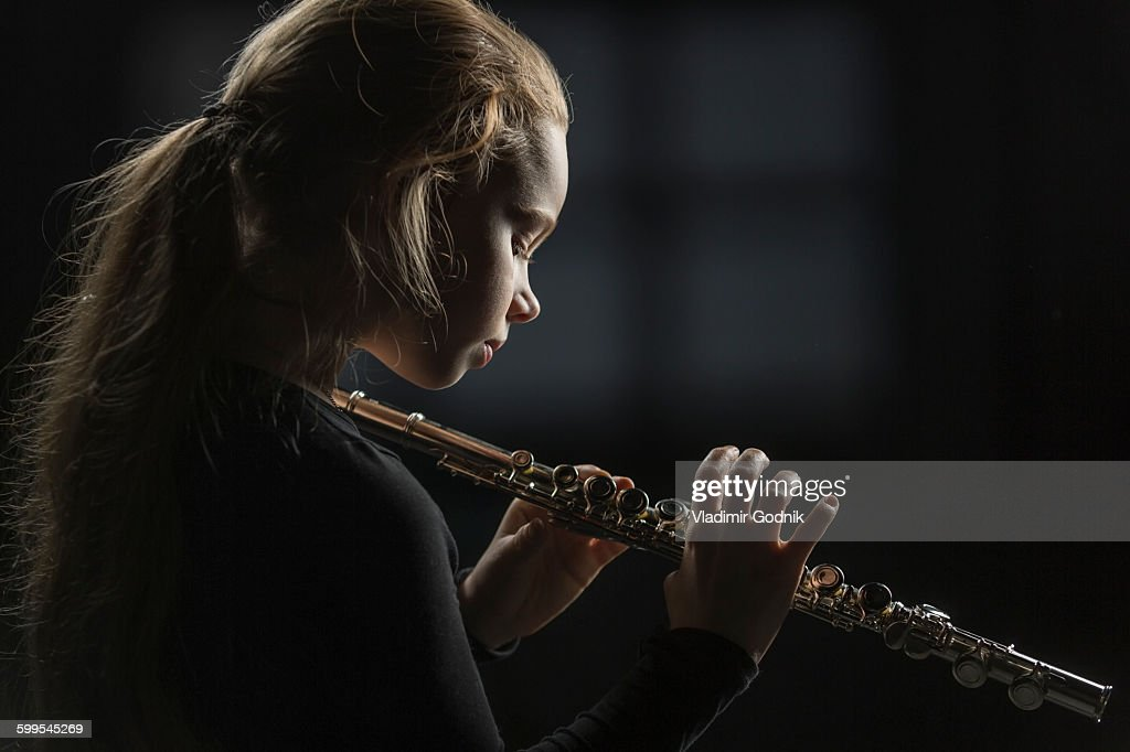 Side view of girl holding flute against black background