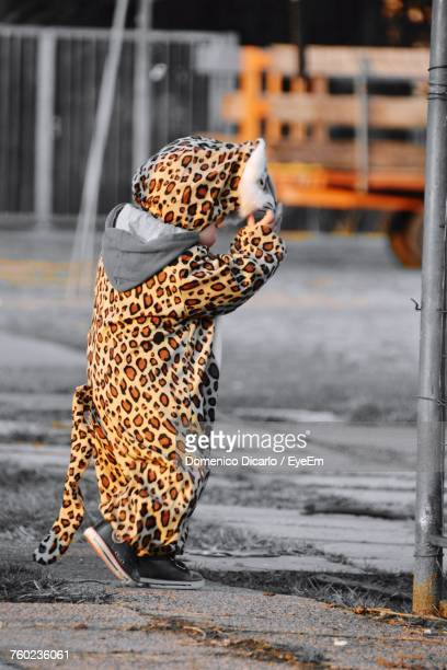 Side View Of Girl In Leopard Costume Standing On Street During Halloween