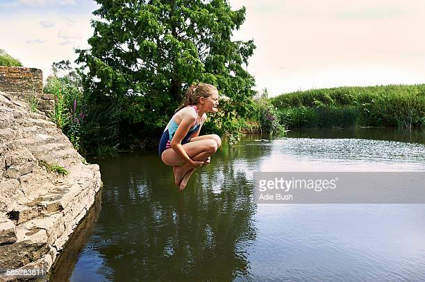 Side view of girl jumping into lake