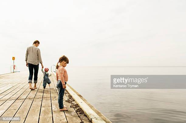side view of girl looking at sea while standing on pier with family walking in background against sky