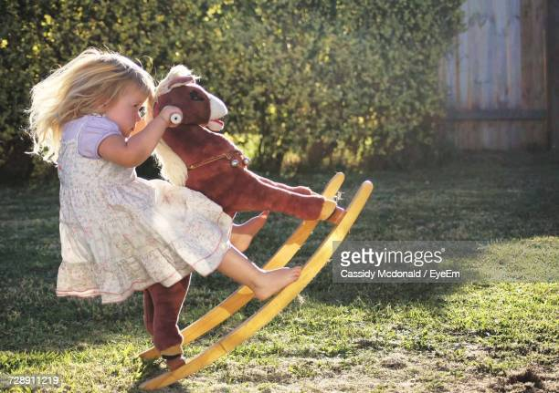 Side View Of Girl Playing On Rocking Horse In Yard