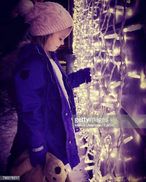 Side View Of Girl Touching Illuminated Decoration During Christmas At Night