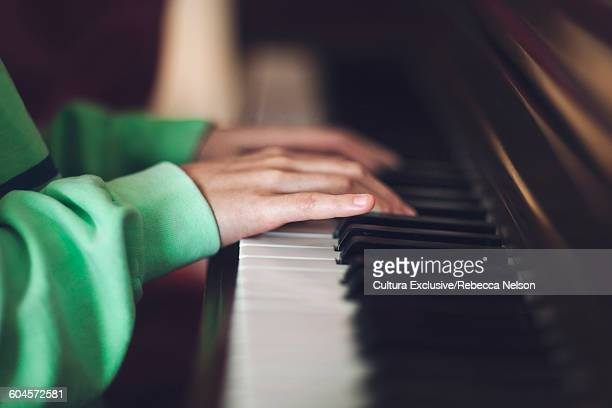 Side view of girls hands playing piano