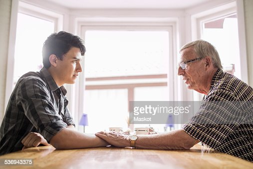 side view of grandfather consoling grandson at table stock foto getty images. Black Bedroom Furniture Sets. Home Design Ideas