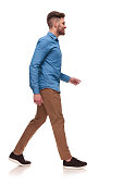 side view of handsome casual man wearing a blue shirt walking on white background