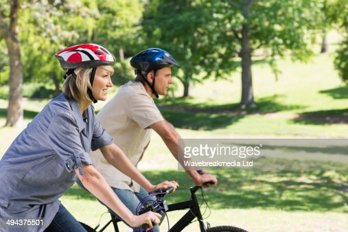 Happy couple cycling in park : Foto de stock