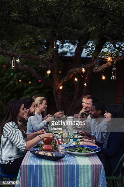 Side view of happy friends having dinner at table in yard