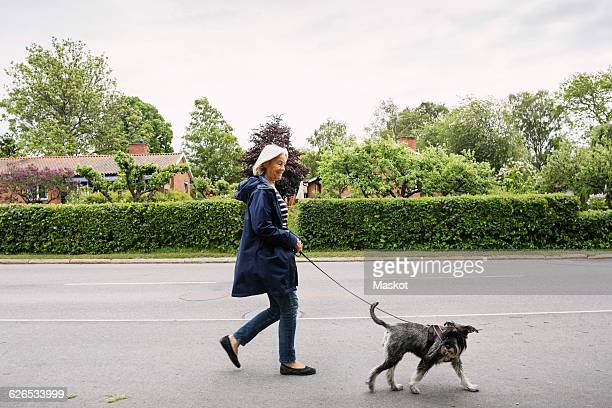 Side view of happy senior woman walking with dog on street