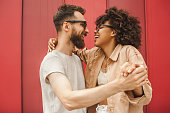 side view of happy young multiethnic couple dancing and holding hands