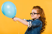 side view of kid in eyeglasses with balloon in hands isolated on yellow