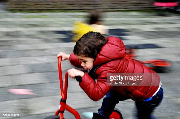 Side View Of Little Boy Riding Tricycle